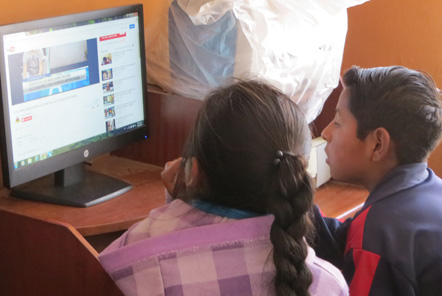Children looking at computer in Peru